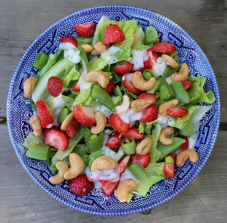 Blue plate holding salad continaing green beans strawberries, cashews, lettuce